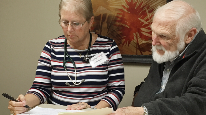 Nurse practitioner Deb Hayes and Dr. John George III confer over a patient chart at the Mary Rose Clinic in Oneida.
