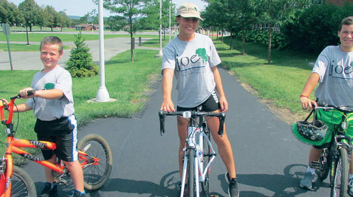 """Sarah Bostick, a leukemia survivor, rides on the Mohawk Valley Community College campus with Dominick Klar during the reception for participants in the third annual """"Ride for Joe."""""""