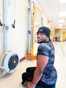 Kevin Burnside, Paralympic hopeful, works out on the ERG machine and bench press at Sitrin Rehabilitation Center in New Hartford.