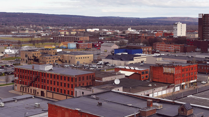 This photo, courtesy of the Observer-Dispatch, shows the location in downtown Utica for the proposed Mohawk Valley Health System hospital. Looking east toward the Doubletree by Hilton Hotel Utica, the tall brick building at upper right, and the Adirondack Bank Center at the Utica Memorial Auditorium (round, white building at left), the campus will cover approximately 25 acres and include State, Lafayette, Cornelia and Columbia streets, along with Broadway.