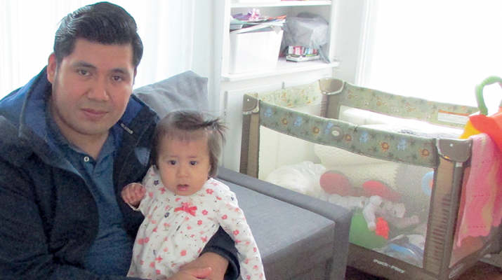 Angel Ramirez holds his baby girl, Ariana, in their home in west Utica.