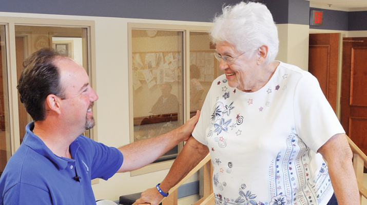 Warren Mundrick, director of rehabilitation at the Masonic Care Community in Utica, assists a patient.