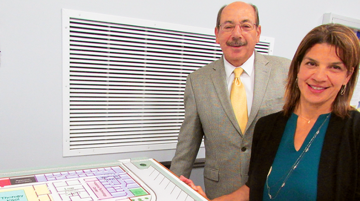 Alicia Dicks, president and CEO of The Community Foundation, and Rudy D'Amico, president and CEO of the Central Association for the Blind and Visually Impaired, look over plans for the new rehabilitation center.