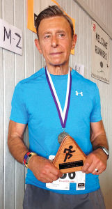 Rich D'Accurzio displays the first-place medal he won in the over-50 age group at the Delta Lake Half-Marathon.