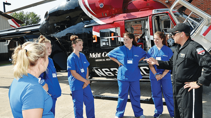 """Sean Byard, right, a pilot for Mercy Flight Central, explains the inner workings of a rescue helicopter to students from the Medical Academy of Science and Health Camp at Rome Memorial Hospital. Twenty-one students from 12 different schools spent three days at the hospital learning about the wide array of health care careers available to interested students. """"The students had an opportunity to meet with health care workers from numerous departments throughout the hospital, talk about their jobs and see them in action in addition to participating in hands-on activities,"""" said Rome Memorial Hospital Director of Education, Volunteer Services and Employee Health Julie Chrysler."""