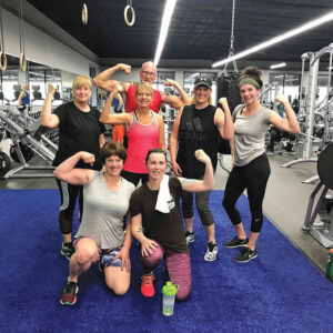 Members of a group fitness class flex their muscles at Revamp Fitness in Herkimer.