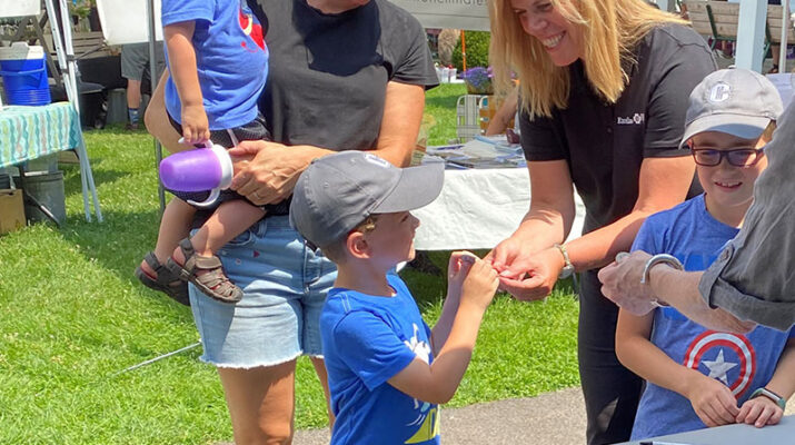 Excellus BlueCross BlueShield Utica Regional President Eve Van de Wal gives Power of Produce Kids Club tokens to the Townsend family (Michelle, Vance, Everett, and Maverick) at the Clinton Farmers Market.