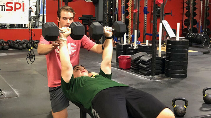 SPI Strength and Conditioning Coach Jared Smaldon (in red T-shirt) trains student athletes at the fitness center, preparing them for the fall sports season.